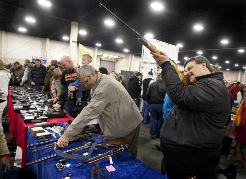 Tim Wilkes, right, looks down the barrel of a hunting rifle during the 2013 Rocky Mountain Gun Show at the South Towne Expo Center in Sandy, Utah Saturday, Jan. 5, 2013. In spite of the recent school shooting in Newtown, Conn., gun enthusiasts packed in by the hundreds to purchase weapons and ammunition. (AP Photo/The Deseret News, Ben Brewer)