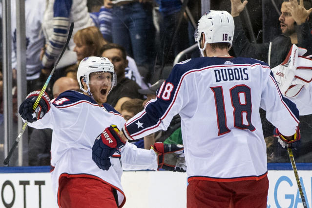 Columbus Blue Jackets center Gustav Nyquist, left, celebrates his game-winning overtime penalty shot with teammate Pierre-Luc Dubois in an NHL hockey game against the Toronto Maple Leafs in Toronto on Monday, Oct. 21, 2019. (Frank Gunn/The Canadian Press via AP)