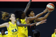 Las Vegas Aces forward Angel McCoughtry (35) drives to the basket after getting around Seattle Storm forward Breanna Stewart (30) and forward Natasha Howard (6) during the first half of Game 1 of basketball's WNBA Finals Friday, Oct. 2, 2020, in Bradenton, Fla. (AP Photo/Chris O'Meara)