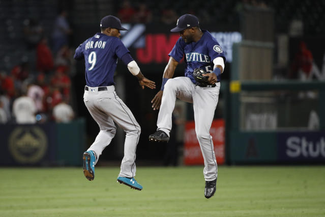 Seattle Mariners' Dee Gordon, left, and Guillermo Heredia celebrate their team's 3-0 win over the Los Angeles Angels in a baseball game Wednesday, July 11, 2018, in Anaheim, Calif. (AP Photo/Jae C. Hong)