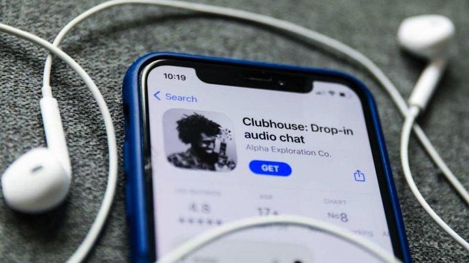 An iPhone running Clubhouse and a pair of headphones