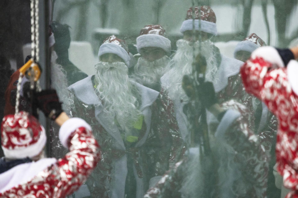 Russian emergency rescue workers dressed as Ded Morozes (Santa Claus, or Father Frost) reflect in a window of a children hospital after scaling the wall to greet children to mark the upcoming New Year celebrations, in Moscow, Russia, Friday, Dec. 25, 2020. Russia, which has so far registered more than 2.9 million confirmed cases of the virus and over 52,000 deaths in the pandemic, has been swept by a rapid resurgence of the outbreak this fall, with numbers of infections and deaths significantly exceeding those reported in the spring. Usually, performers come into children's rooms, but this year because of the virus-related restrictions, the artists had to perform outside of the hospital at a significant distance. (AP Photo/Pavel Golovkin)