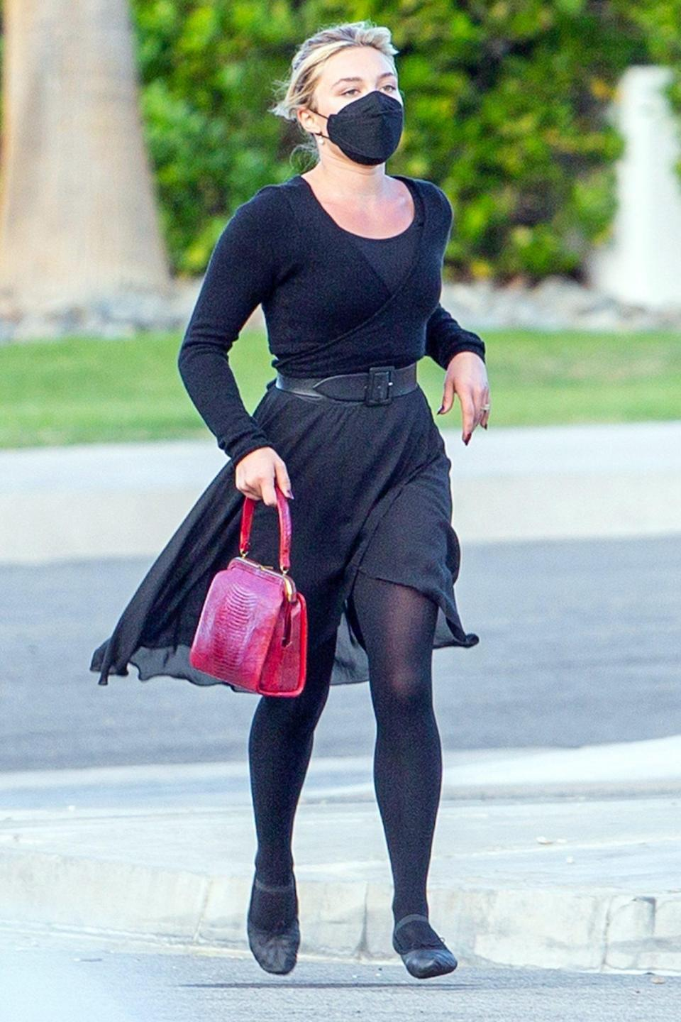 <p>Florence Pugh springs into action during a scene on the set of <em>Don't Worry Darling</em> on Wednesday in Palm Springs, California.</p>