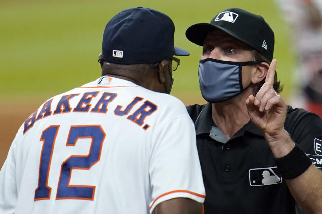 Umpire Chris Guccione, right, talks to Houston Astros manager Dusty Baker (12) after both benches emptied onto the field after the sixth inning of a baseball game against the Los Angeles Dodgers Tuesday, July 28, 2020, in Houston. (AP Photo/David J. Phillip)