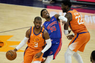 Phoenix Suns guard Chris Paul (3) drives as Detroit Pistons guard Delon Wright (55) is blocked by center Deandre Ayton (22) during the second half of an NBA basketball game, Friday, Feb. 5, 2021, in Phoenix. (AP Photo/Matt York)