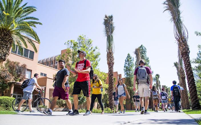 Arizona State University students take Palm Walk between classes on the Tempe campus in September 2017.