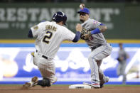 New York Mets' Javier Baez, right, tags out Milwaukee Brewers' Luis Urias (2) at second base as he throws to first to turn a double play during the sixth inning of a baseball game Saturday, Sept. 25, 2021, in Milwaukee. (AP Photo/Aaron Gash)