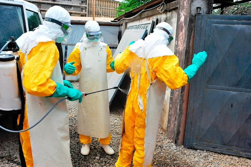 Medical staff clean their protection suits as part of the fight against the Ebola virus at the Donka hospital in Conakry on March 8, 2015