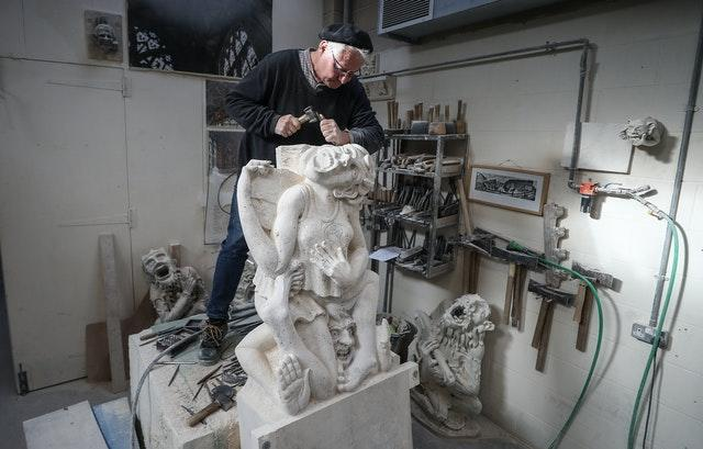Master mason Pascal Mychalysin works on a gargoyle holding a cheese, to represent the Cheese Rollers of Gloucestershire, as part of a project for Gloucester Cathedral to depict local areas in a more modern way