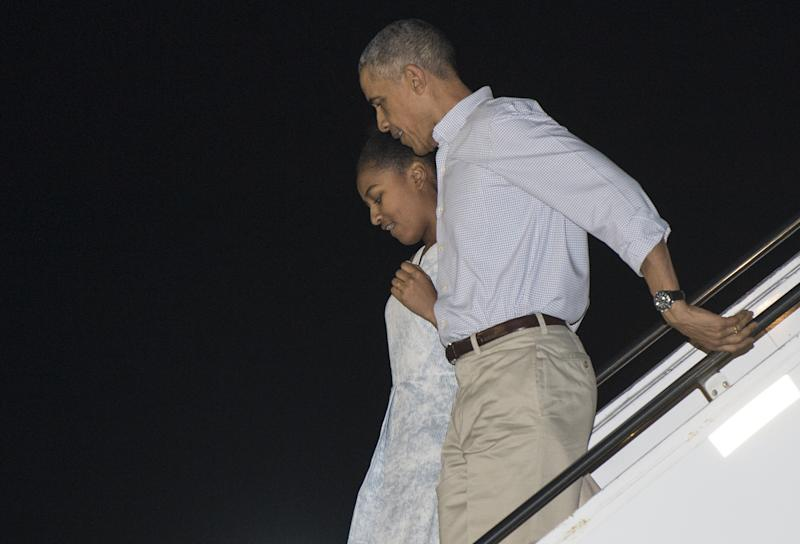 US President Barack Obama and daughter Sasha step off Air Force One upon their arrival at Joint Base Pearl Harbor-Hickam in Honolulu on December 19, 2014