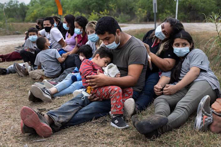 A Guatemalan family waits with fellow immigrants to board a U.S. Customs and Border Protection bus to a processing center after crossing the border from Mexico April 13 in La Joya, Texas.