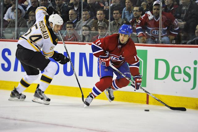 MONTREAL, QC - APRIL 18: Scott Gomez #11 of the Montreal Canadiens controls the puck in behind the net while being pursued by Adam McQuaid #54 of the Boston Bruins in Game Three of the Eastern Conference Quarterfinals during the 2011 NHL Stanley Cup Playoffs at Bell Centre on April 18, 2011 in Montreal, Canada. (Photo by Phillip MacCallum/Getty Images)