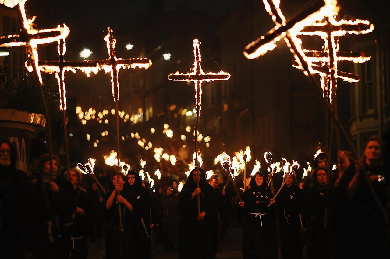 LEWES, ENGLAND - NOVEMBER 05:  Revelers walk with burning crosses during the Bonfire Night celebrations on November 5, 2012 in Lewes, Sussex in England. Bonfire Night is related to the ancient festival of Samhain, the Celtic New Year. Processions held across the South of England culminate in Lewes on November 5, commemorating the memory of the seventeen Protestant martyrs. Thousands of people attend the parade as Bonfire Societies parade through the narrow streets until the evening comes to an end with the burning of an effigy, or 'guy,' usually representing Guy Fawkes, who died in 1605 after an unsuccessful attempt to blow up The Houses of Parliament.  (Photo by Dan Kitwood/Getty Images)