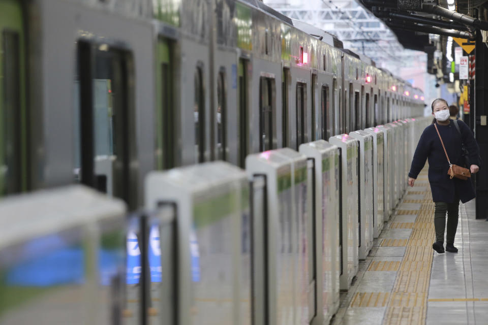 A woman wearing a face mask to protect against the spread of the coronavirus walks along a platform at the train station in Tokyo, Wednesday, Nov. 25, 2020. (AP Photo/Koji Sasahara)