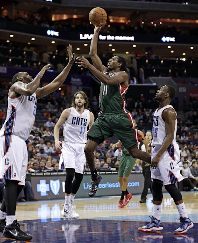 Milwaukee Bucks' Brandon Knight, second from right, shoots between Charlotte Bobcats' Al Jefferson, left, Kemba Walker, right, and Josh McRoberts, back, during the second half of an NBA basketball game in Charlotte, N.C., Monday, Dec. 23, 2013. The Bobcats won 111-110 in overtime. (AP Photo/Chuck Burton)