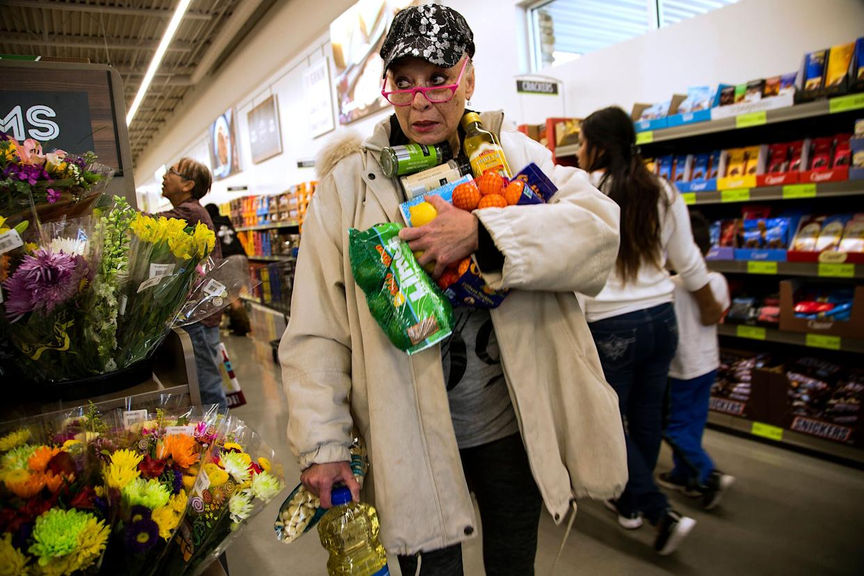 Janelle Myers fills her arms with groceries during the grand opening of Aldi food market on March 24, 2016 in Moreno Valley, California. (Photo: Gina Ferazzi via Getty Images)