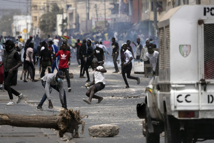 Demonstrators clash with riot policemen during protests against the arrest of opposition leader and former presidential candidate Ousmane Sonko in Dakar, Senegal, Friday, March 5, 2021. Days of violent protests in Senegal have killed at least one person, local reports say, as young people take to the streets nationwide in support of the main opposition leader who was detained Wednesday. (AP Photo/Leo Correa)