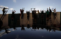 FILE - In this Oct. 4, 2020 file photo fans, standing on ladders from behind the fence, celebrate a goal as they watch a Czech first division match between Bohemians Prague and Zlin in Prague, Czech Republic. Czechs had been assured it wouldn't happen again. But amid a record surge of coronavirus infections that's threatening the entire health system with collapse, the Czech Republic is adopting on Thursday exactly the same massive restrictions it slapped on citizens in the spring. (AP Photo/Petr David Josek)