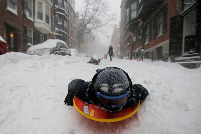 <p>A boy sleds down a Beacon Hill street during Storm Grayson in Boston, Mass., Jan. 4, 2018. (Photo: Brian Snyder/Reuters) </p>