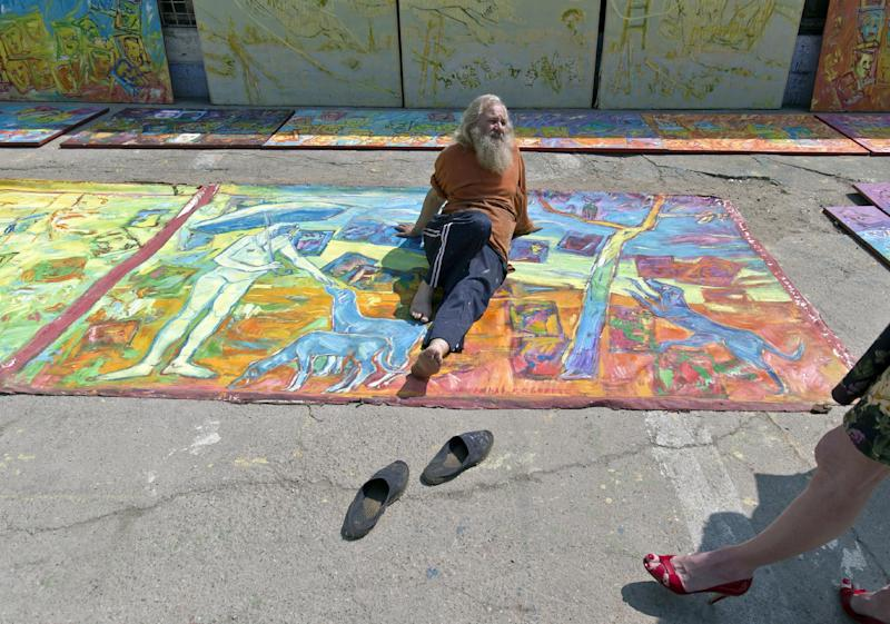 In this photo taken on April 4, 2013, Romanian artist Vasile Muresan, known as Murivale sits on one of his paintings in a parking lot, in Bucharest, Romania. The white-bearded painter can often be seen sitting on his colorful canvasses which he displays in the street followed by the street dogs which are his companions and also inspire his work. The 56-year-old, whose home city is Bistrita_the Transylvanian town associated with the legendary Count Dracula_ has been painting with passion since he was a teen, producing vivid works of Monaco, the streets of Paris, the hurly burly of the Romanian capital and huge colorful more abstract canvasses. (AP Photo/Vadim Ghirda)