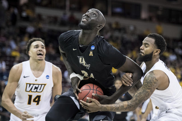Central Florida center Tacko Fall (24) is fouled by VCU guard Mike'L Simms, right, during the second half of a first-round game in the NCAA men's college basketball tournament Friday, March 22, 2019, in Columbia, S.C. Central Florida won 73-58. (AP Photo/Sean Rayford)