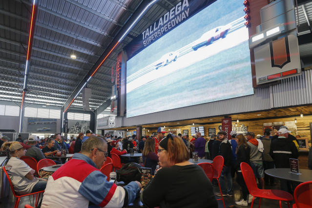 Fans watch jumbotrons as they eat before the 1000Bulbs.com 500 at Talladega Superspeedway, Sunday, Oct 13, 2019, in Talladega, Ala. (AP Photo/Butch Dill)