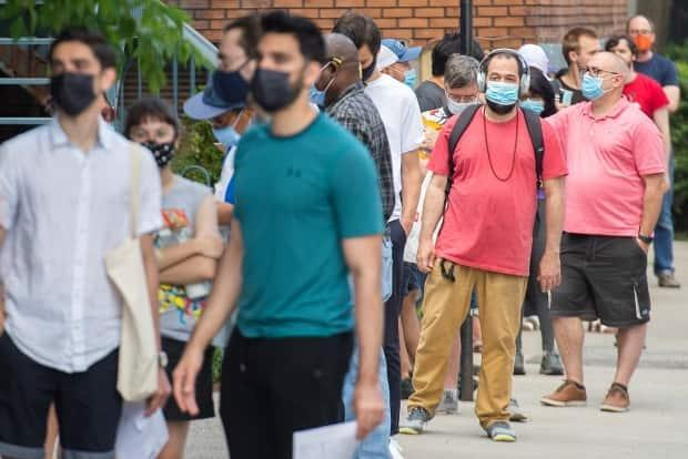 People wear face masks as they line up for a COVID-19 vaccine shot at an outdoor clinic in Montreal. (Graham Hughes/The Canadian Press - image credit)