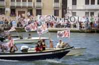"""""""No Big Ships"""" activists stage a protest as the MSC Orchestra cruise ship leaves Venice, Italy, Saturday, June 5, 2021. The 92,409-ton, 16-deck MSC Orchestra cruise ship, the first cruise ship leaving Venice since the pandemic is set to depart Saturday amid protests by activists demanding that the enormous ships be permanently rerouted out the fragile lagoon, especially Giudecca Canal through the city's historic center, due to environmental and safety risks. The ship passed two groups of protesters: pro-cruise advocates whose jobs depend on the industry as well as protesters who have been campaigning for years to get cruise ships out of the lagoon. (AP Photo/Antonio Calanni)"""