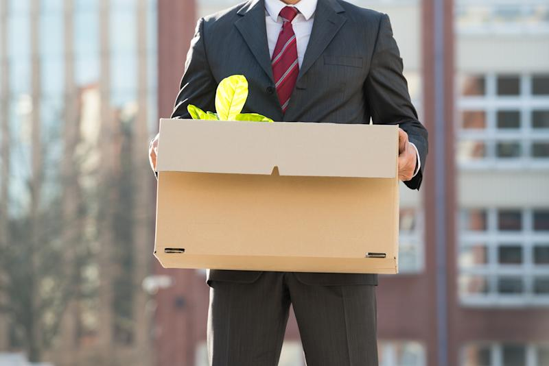 Close-up Of Businessperson Standing With Cardboard Box Outside Office