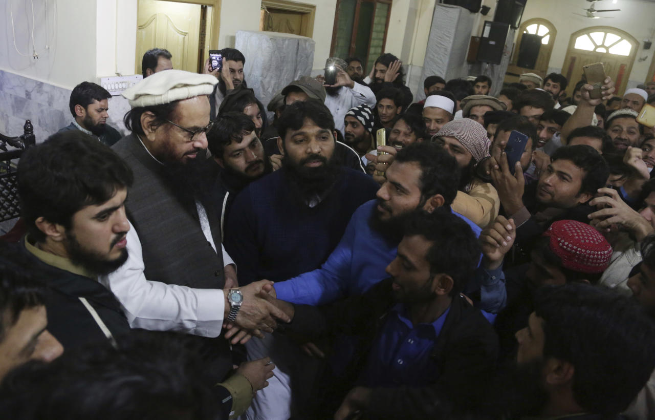 Supporters of Hafiz Saeed, second from left, head of the Pakistani religious party, Jamaat-ud-Dawa, greet their leader as he arrived at a mosque in Lahore, Pakistan, Friday, Nov. 24, 2017. Pakistani authorities acting on a court order released a U.S.-wanted militant Friday who allegedly founded a banned group linked to the 2008 Mumbai, India attack that killed 168 people, his spokesman and officials said. (AP Photo/K.M. Chaudary)
