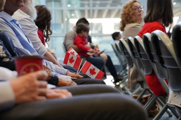 New Canadians take part in a pre-pandemic citizenship ceremony. (Stephen Lubig/CBC - image credit)