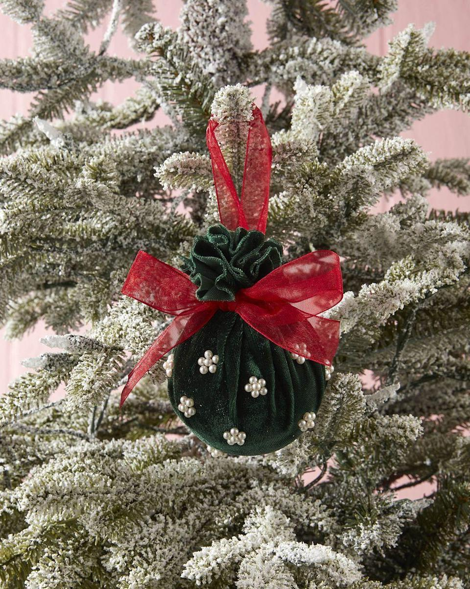 """<p>The perfect sophisticated touch for that friend who favors cultivated over cute, this velvet ornament is sure to be a Christmas hit.</p><p><strong>To make:</strong> Cut a square of velvet fabric. Wrap around a ball ornament, cinching it at the top. Tie a piece of ribbon around the cinch to hold closed and create a hanger. Tie a bow from the same ribbon and attach with hot glue. Attach small pearl craft bead with hot glue.</p><p><a class=""""link rapid-noclick-resp"""" href=""""https://www.amazon.com/Kanzueri-Bracelet-Necklaces-Jewelry-Repairing/dp/B091F3WXB5/ref=sr_1_4?tag=syn-yahoo-20&ascsubtag=%5Bartid%7C10050.g.645%5Bsrc%7Cyahoo-us"""" rel=""""nofollow noopener"""" target=""""_blank"""" data-ylk=""""slk:SHOP SMALL PEARL BEADS"""">SHOP SMALL PEARL BEADS</a></p>"""