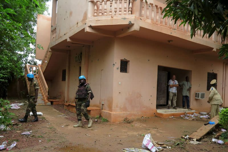 FILE PHOTO: Malian soldiers survey the damage after a hotel siege over the weekend in which 17 people died in Sevare
