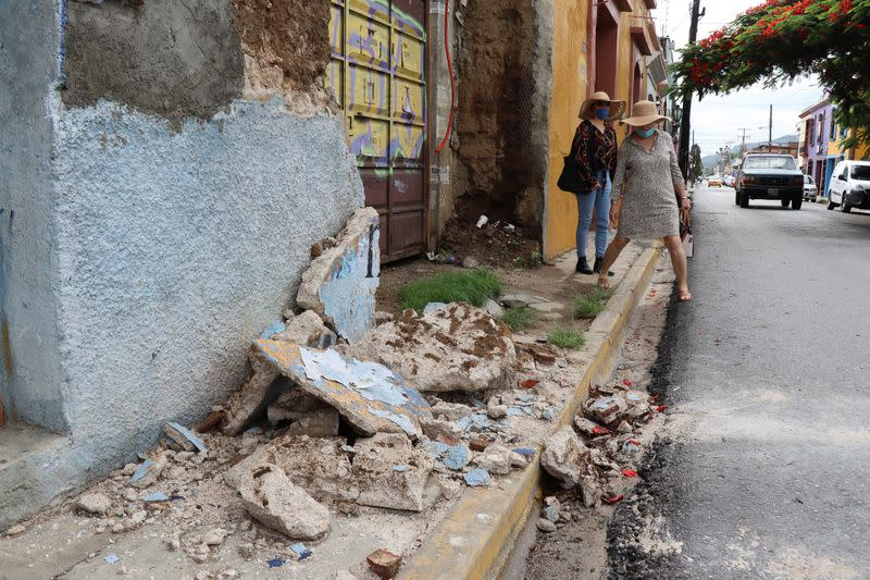 Women walk by a building damaged during a quake, in Oaxaca