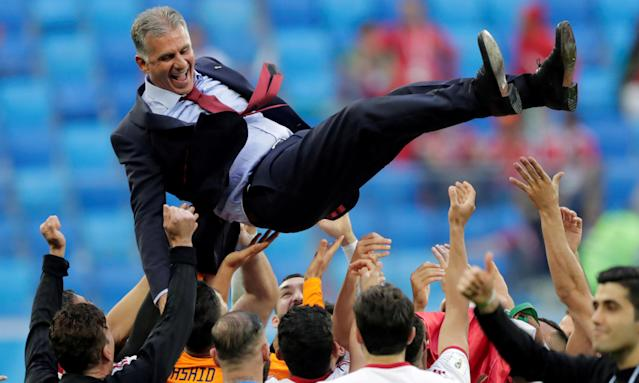 Iran players throw Carlos Queiroz in the air after kicking off their World Cup with a 1-0 win over Morocco in St Petersburg.