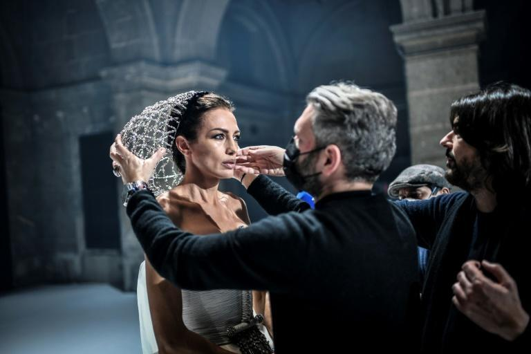 French designer Stephane Rolland adjusts a headpiece on a model during the shooting of a film designed to replace Haute Couture fashion shows in Paris on January 18, 2021