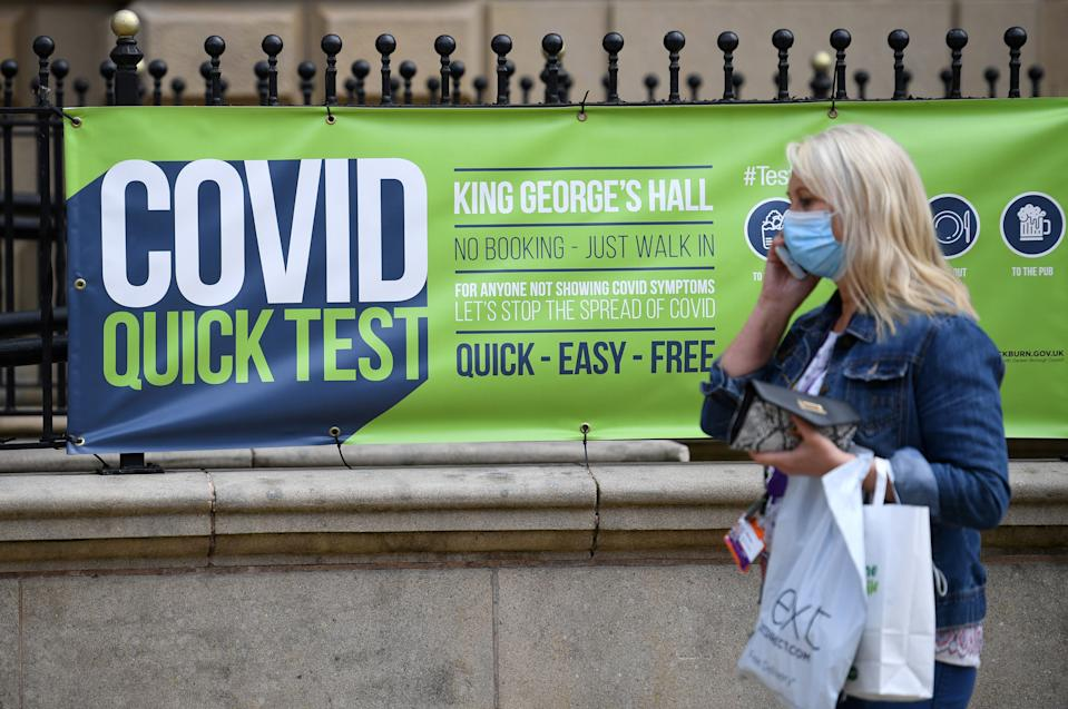 A pedestrian wearing a face covering walks past a sign for a walk-in Covid-19 testing centre in Blackburn, north west England on June 16, 2021. - The UK government on Monday announced a four-week delay to the full lifting of coronavirus restrictions in England due to a surge in infections caused by Delta, which first appeared in India. (Photo by Oli SCARFF / AFP) (Photo by OLI SCARFF/AFP via Getty Images)