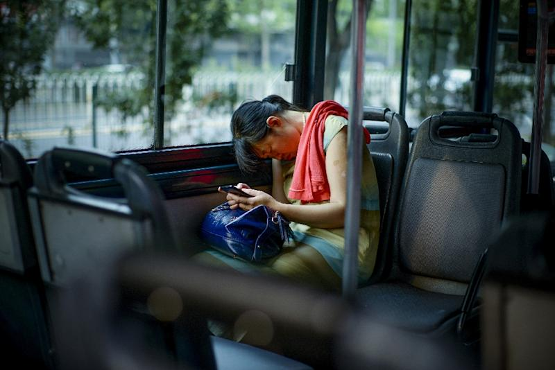 A passenger holds her mobile phone while asleep on a bus in Beijing (AFP Photo/Wang Zhao)