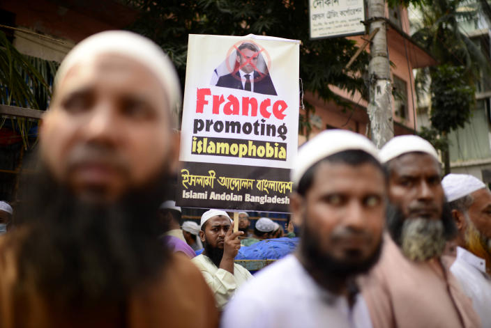 Supporters of Islami Andolan Bangladesh, an Islamist political party, carry a defaced poster of French President Emmanuel Macron as they protest against the publishing of caricatures of the Prophet Muhammad they deem blasphemous, in Dhaka, Bangladesh, Tuesday, Oct. 27, 2020. Muslims in the Middle East and beyond on Monday called for boycotts of French products and for protests over the caricatures, but Macron has vowed his country will not back down from its secular ideals and defense of free speech. (AP Photo/Mahmud Hossain Opu)