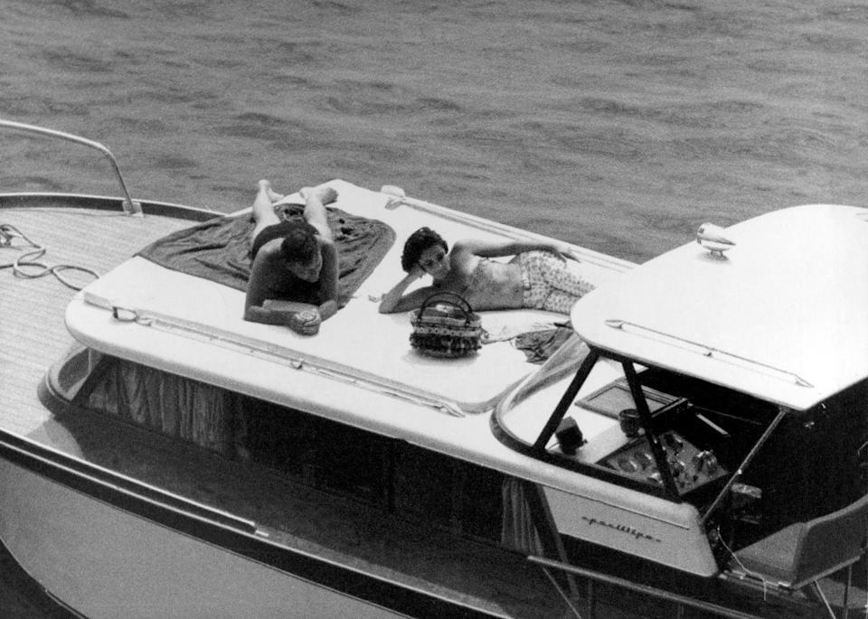 <p>Elizabeth Taylor lounges on the deck of her yacht with actor Richard Burton. The actress wears a strapless bikini top and floral pants. </p>