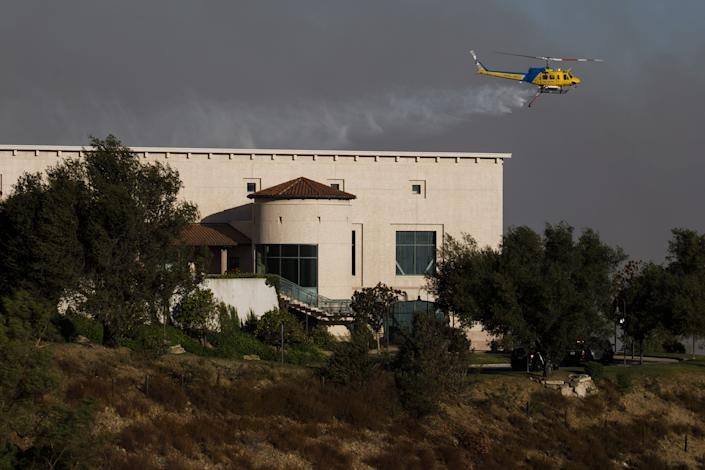 A helicopter drops water to protect the Ronald Reagan Presidential Library during the Easy Fire in Simi Valley, Calif. on Oct. 30, 2019. (Photo: Patrick T. Fallon/Bloomberg via Getty Images)