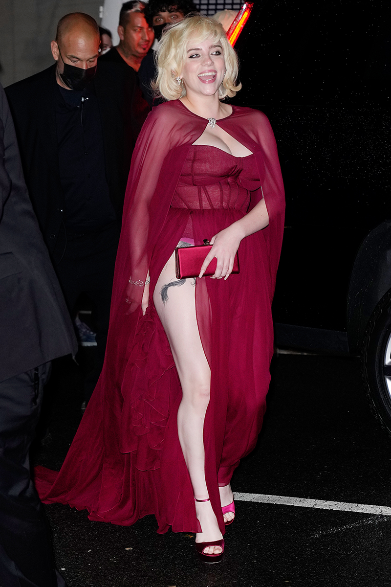 <p>Continuing her truly stellar fashion streak, Billie wowed for another time at the 2021 Met Gala after-party wearing this HEAVENLY crimson second gown, complete with a hip-high split, a sheer cape and matching peep-toe heels. On closer inspection, you can see that the split also reveals the a slither of her 'secret tattoo' on Billie's upper thigh - how cool! Bow down, people - this is Billie's world, we're just living in it. </p>