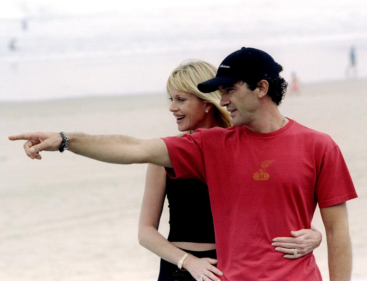 """Spain's international actor Antonio Banderas (R) makes a point to his American wife Melanie Griffith as they pose for photographers at San Sebastian's Zurriola beach September 17, 1999. Banderas'first film """"Crazy in Alabama"""" will compete in San Sebastian's International Film Festival.  REUTERS/Pablo Sanchez"""