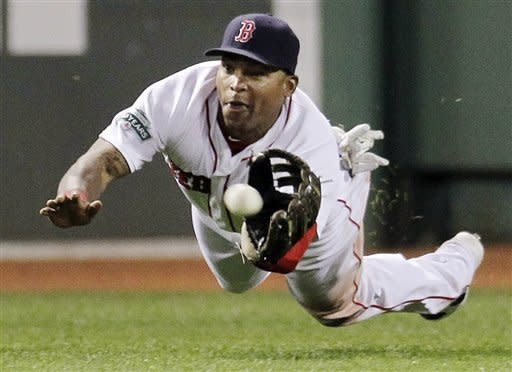Boston Red Sox center fielder Marlon Byrd dives to catch a fly ball by Detroit Tigers' Gerald Laird during the eighth inning of a baseball game at Fenway Park in Boston, Wednesday, May 30, 2012. (AP Photo/Elise Amendola)