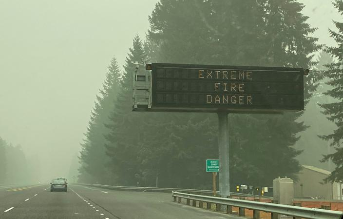 A fire warning sign is seen through the smoke in Sandy, Oregon, on Monday, Sept. 14, 2020.