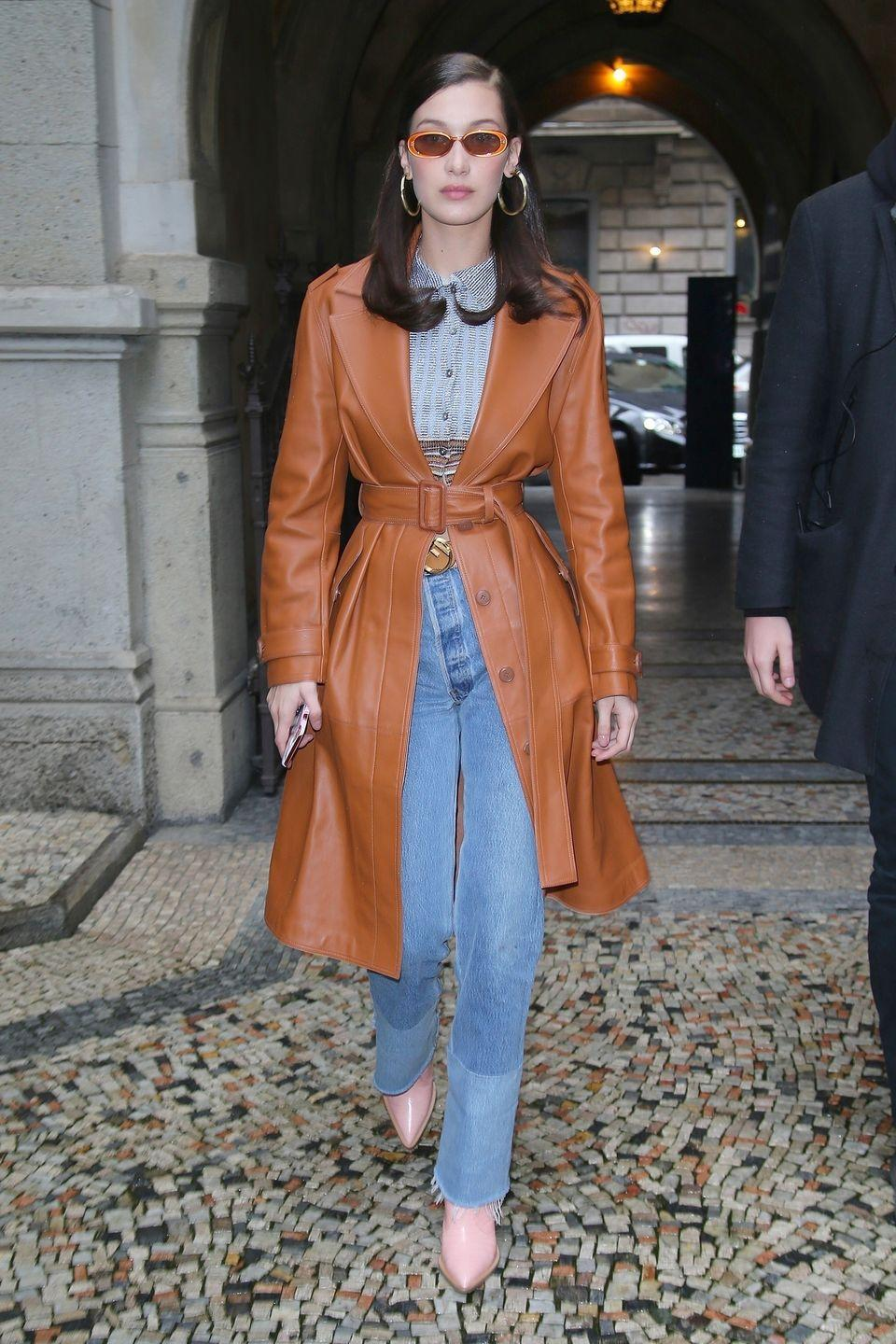 <p>In a burnt orange patent leather belted jacket cinched at the waist, layered over a blue collared shirt tucked into high-waisted boot-cut frayed jeans, finished with pointed-toe rose-colored boots, gold hoop earrings, and orange sunglasses while on the streets of Milan.</p>