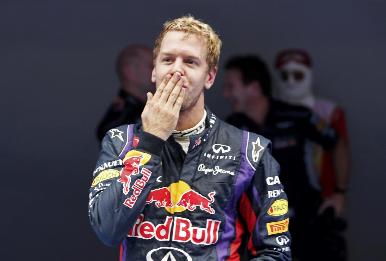 Red Bull Formula One driver Sebastian Vettel (C) of Germany blows a kiss as he celebrates winning the Indian F1 Grand Prix at the Buddh International Circuit in Greater Noida, on the outskirts of New Delhi, October 27, 2013.  Vettel became Formula One's youngest four-times world champion on Sunday after winning the Indian Grand Prix for Red Bull. REUTERS/Adnan Abidi (INDIA - Tags: SPORT MOTORSPORT F1)