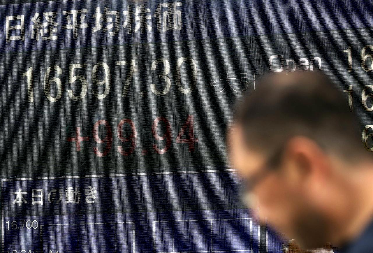 A man walks past an electronic stock board showing Japan's Nikkei 225 index at a securities firm in Tokyo, Japan, Wednesday, Aug. 24, 2016. Asian stocks meandered Wednesday as investors awaited fresh cues from Federal Reserve on the outlook for interest rates. Markets were steady following the submarine launch of a ballistic missile by North Korea. (AP Photo/Eugene Hoshiko)