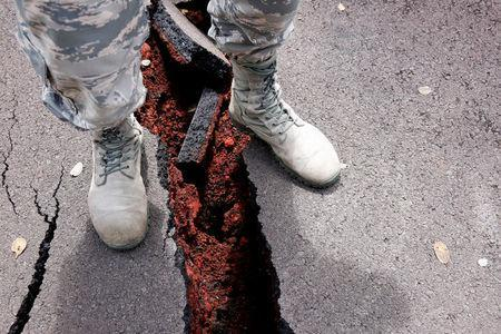 A soldier of the Hawaii National Guard stands over a crack in a road in Leilani Estates during ongoing eruptions of the Kilauea Volcano in Hawaii, U.S., May 18, 2018. REUTERS/Terray Sylvester