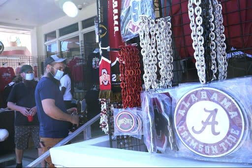 Football fans shop for souvenirs, Sunday, Jan. 10, 2020, in Miami Beach, Fla. Ohio State, and Alabama will play the College Football Playoff National Championship game in Miami Gardens on Monday night. (AP Photo/Marta Lavandier)